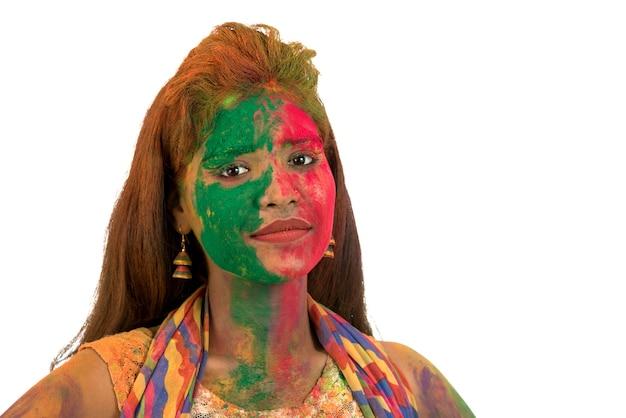 Portret van een gelukkig jong meisje met een kleurrijk gezicht op holi-kleurenfestival op witte achtergrond