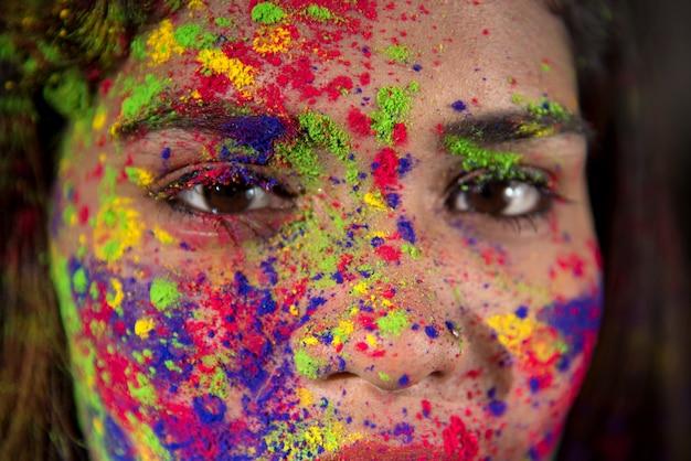 Portret van een gelukkig jong meisje met een kleurrijk gezicht ter gelegenheid van holi kleur festival.