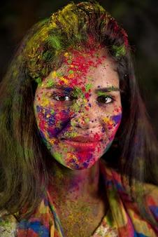 Portret van een gelukkig jong meisje met een kleurrijk gezicht ter gelegenheid van holi-kleurenfestival