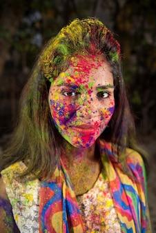 Portret van een gelukkig jong meisje met een kleurrijk gezicht ter gelegenheid van holi-kleurenfestival.