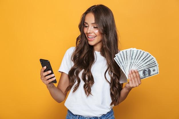Portret van een gelukkig jong meisje met lang donkerbruin haar dat zich over gele muur bevindt, die geldbankbiljetten houdt, die mobiele telefoon gebruikt