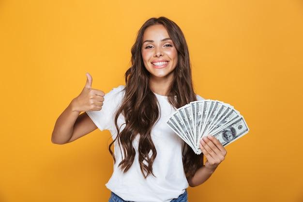 Portret van een gelukkig jong meisje met lang donkerbruin haar dat zich over gele muur bevindt, geldbankbiljetten houdt, duimen toont