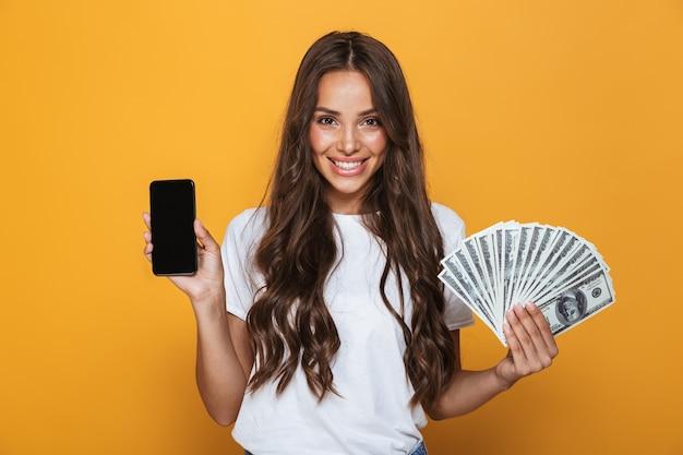 Portret van een gelukkig jong meisje met lang donkerbruin haar dat zich over gele muur bevindt, geldbankbiljetten houdt, leeg scherm mobiele telefoon toont