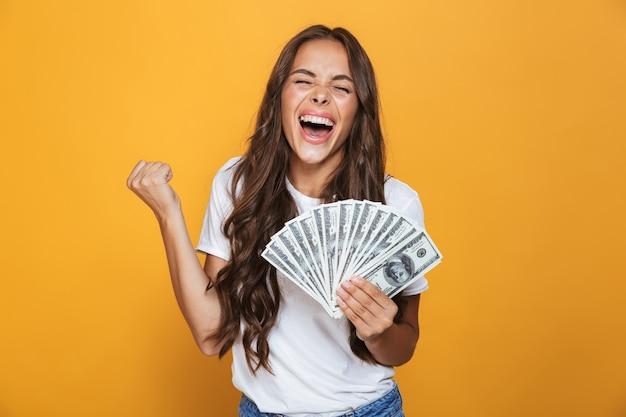 Portret van een gelukkig jong meisje met lang donkerbruin haar dat zich over gele muur bevindt, geldbankbiljetten houdt, viert