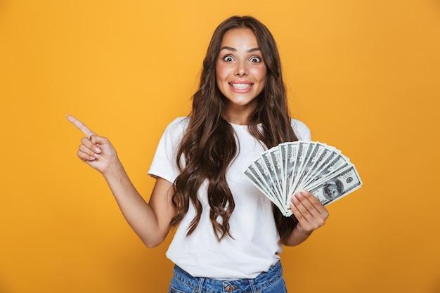 Portret van een gelukkig jong meisje met lang donkerbruin haar dat zich over gele muur bevindt, geldbankbiljetten houdt, weg wijzend