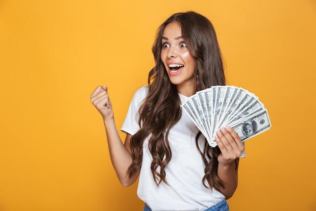 Portret van een gelukkig jong meisje met lang donkerbruin haar dat zich over gele muur bevindt, geldbankbiljetten houdt, wegkijkend