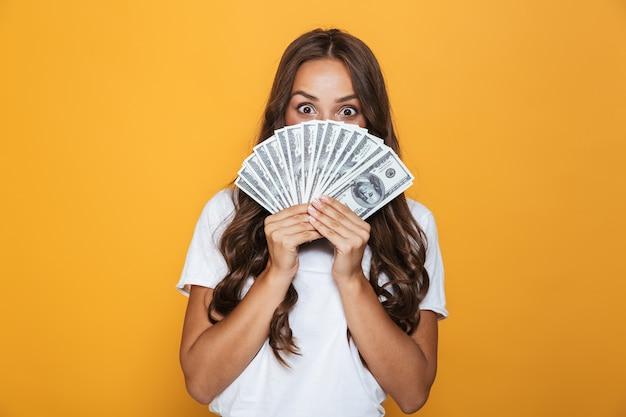 Portret van een gelukkig jong meisje met lang donkerbruin haar dat zich over gele muur bevindt, geldbankbiljetten houdt