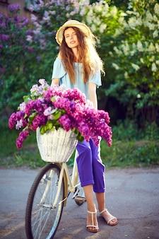Portret van een gelukkig jong meisje met vintage fiets en bloemen op de achtergrond van de stad in het zonlicht buiten.