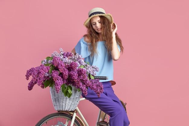 Portret van een gelukkig jong meisje met vintage fiets en bloemen op roze achtergrond.