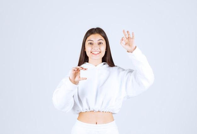 Portret van een gelukkig jong meisjesmodel met een kaart die ok gebaar toont.