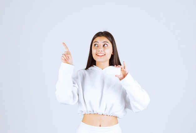 Portret van een gelukkig jong meisjesmodel met een kaart die omhoog wijst.