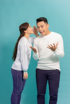 Portret van een gelukkig jong paar die zich over blauw verenigen, geheimen vertellen