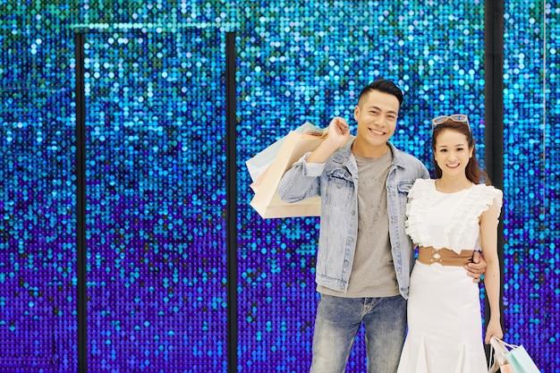 Portret van een gelukkig jong vietnamees paar met boodschappentassen die zich bij fonkelende blauwe muur bevinden