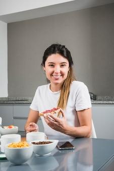 Portret van een gelukkig jong vrouw met brood met jam aan ontbijttafel