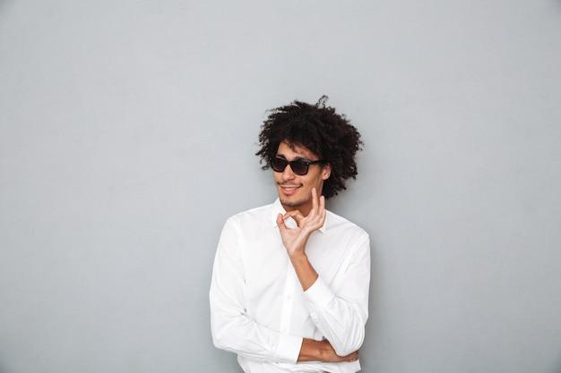 Portret van een gelukkig jonge afrikaanse man in wit overhemd