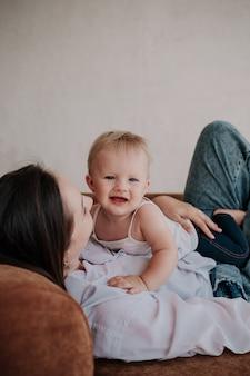 Portret van een gelukkig kind dat op een donkerbruine moeder ligt