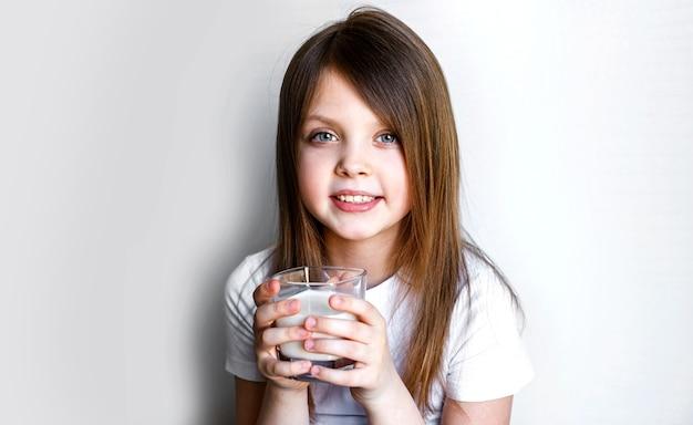 Portret van een gelukkig kind dat vrolijk lacht met een glas melk