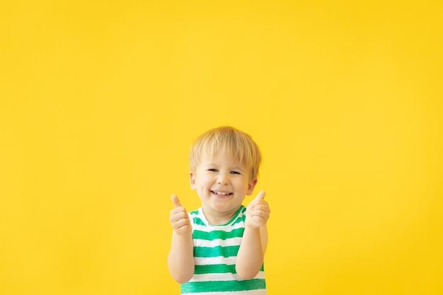 Portret van een gelukkig kind duimen opdagen tegen gele muur op zomervakantie.