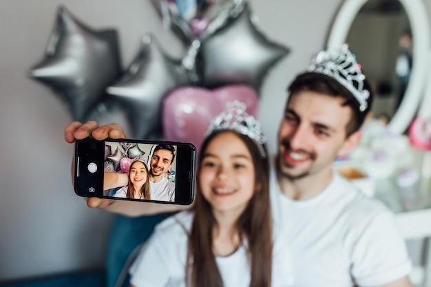 Portret van een gelukkig kind maakt thuis een selfie, terwijl je met papa speelt