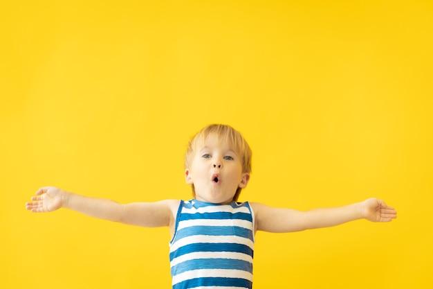 Portret van een gelukkig kind tegen gele muur op zomervakantie.