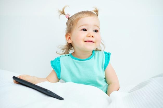 Portret van een gelukkig kind thuis en met een telefoon