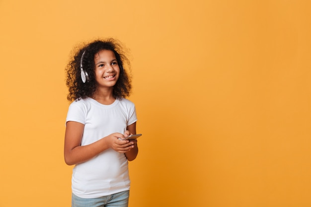 Portret van een gelukkig klein afrikaans meisje dat aan muziek luistert