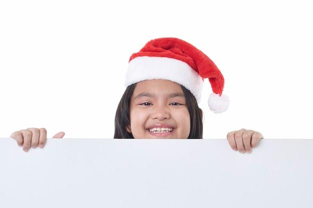 Portret van een gelukkig klein meisje met kerstmuts poseren achter een wit paneel geïsoleerd op wit