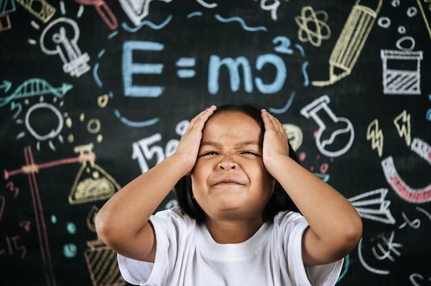 Portret van een gelukkig klein schoolkind legde haar hand op het hoofd