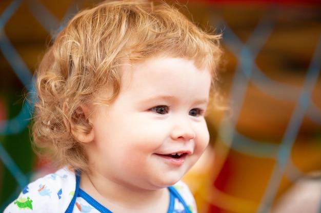 Portret van een gelukkig lachend babykind op zonnige dag. close-up van positieve kinderen op de speelplaats. glimlachende baby, schattige glimlach.