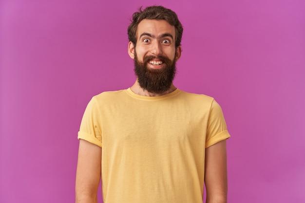 Portret van een gelukkig lachend gezicht, bebaarde jongeman, emotie verbaasd of verbaasde glimlach staand