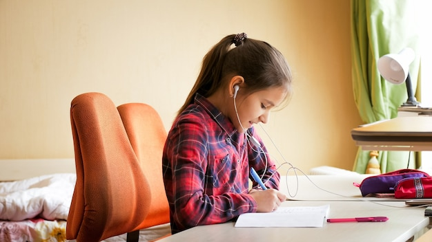 Portret van een gelukkig lachend meisje dat naar muziek luistert terwijl ze schoolhuiswerk doet in de slaapkamer.