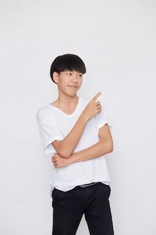 Portret van een gelukkig lachende aziatische man met casual wit t-shirt wijzende hand naar lege ruimte naast op witte achtergrond