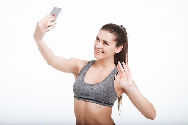 Portret van een gelukkig lachende fitness vrouw zwaaiend naar haar mobiele telefoon geïsoleerd