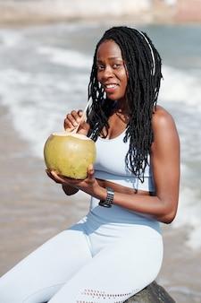 Portret van een gelukkig lachende fitte vrouw die een verfrissende kokoscocktail drinkt na een buitentraining op het strand