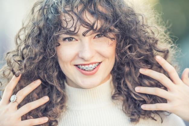 Portret van een gelukkig lachende jonge vrouw met beugels en en krullend haar.