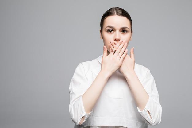 Portret van een gelukkig lachende jonge zakenvrouw die haar mond bedekt met de hand, geïsoleerd over een witte muur