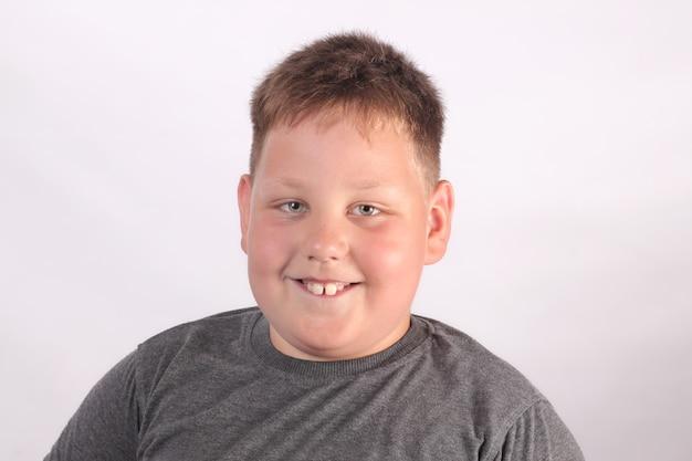 Portret van een gelukkig lachende jongen met autisme op een lichtgrijze achtergrond die naar de camera kijkt