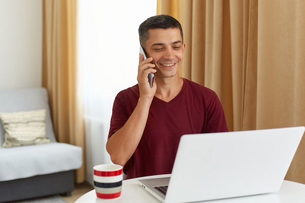 Portret van een gelukkig lachende knappe man die voor een witte laptop zit en met iemand praat via een smartphone, een man met een kastanjebruin casual t-shirt, die thuis in de woonkamer poseert.
