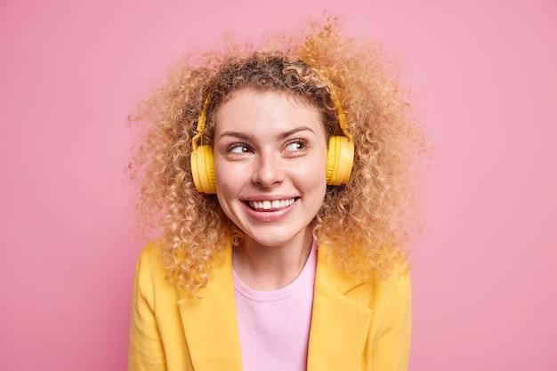 Portret van een gelukkig lachende, krullende vrouw geniet van favoriete afspeellijst, luistert naar muziek via een draadloze koptelefoon kijkt weg en grijnst naar de camera