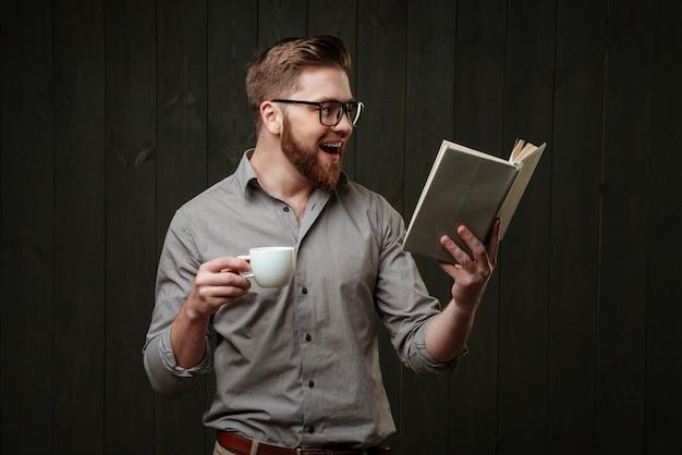 Portret van een gelukkig lachende man in een bril die een boek leest en een kopje koffie vasthoudt op een zwart houten oppervlak