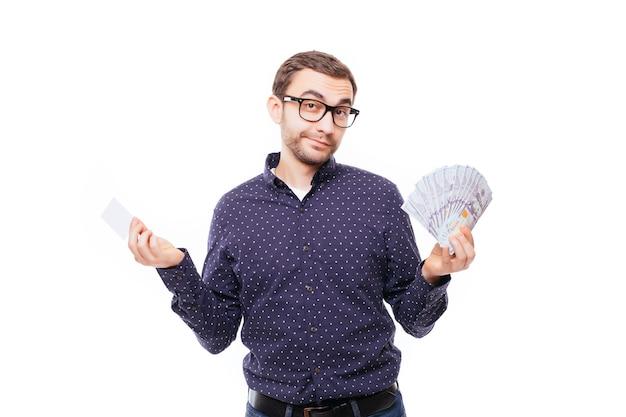 Portret van een gelukkig lachende man in een bril die een hoop geldbankbiljetten vasthoudt en een creditcard toont die over een witte muur wordt geïsoleerd