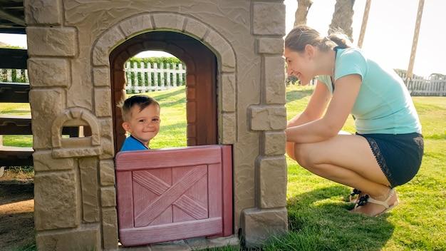 Portret van een gelukkig lachende peuterjongen die speelt in een plastic speelgoedhuis op de kinderspeelplaats in het park