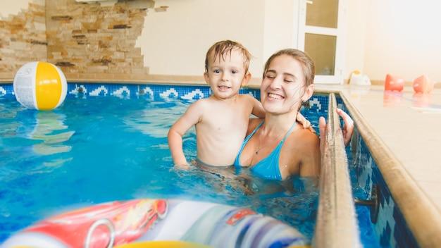 Portret van een gelukkig lachende peuterjongen die speelt met een opblaasbare kleurrijke strandbal met moeder in een overdekt zwembad