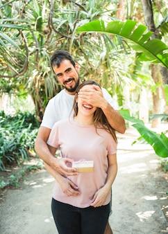 Portret van een gelukkig man die verrassing met cadeau voor zijn vriendin in het bos