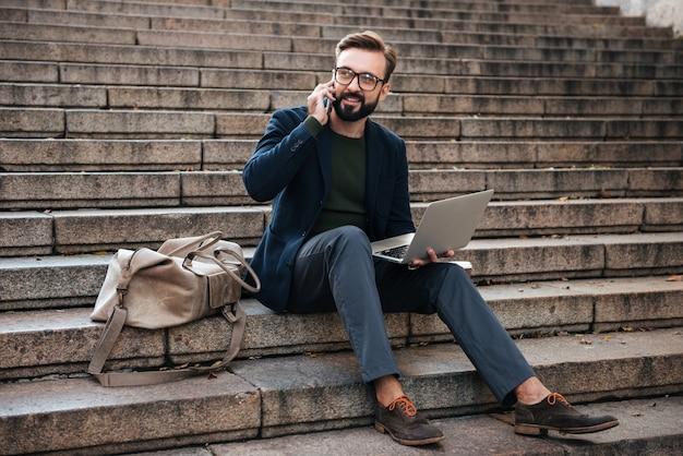 Portret van een gelukkig man in brillen die op laptop werkt