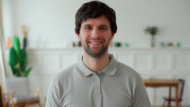 Portret van een gelukkig man in een grijs shirt kijken naar de camera en glimlachen