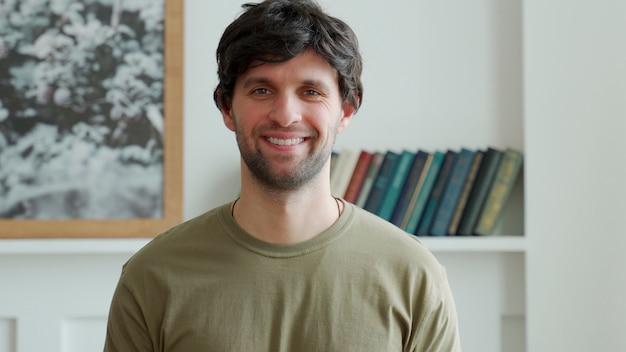 Portret van een gelukkig man in een groene jas kijkt naar de camera en glimlacht