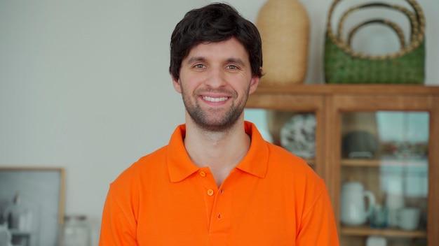 Portret van een gelukkig man in een oranje overhemd kijken naar de camera en glimlachen