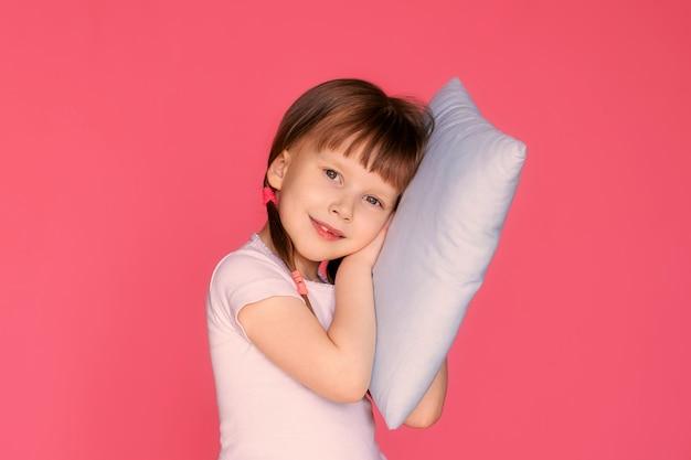 Portret van een gelukkig meisje 5-6 jaar oud op een roze muur met een kussen in haar handen, het kind bereidt zich voor op bed.