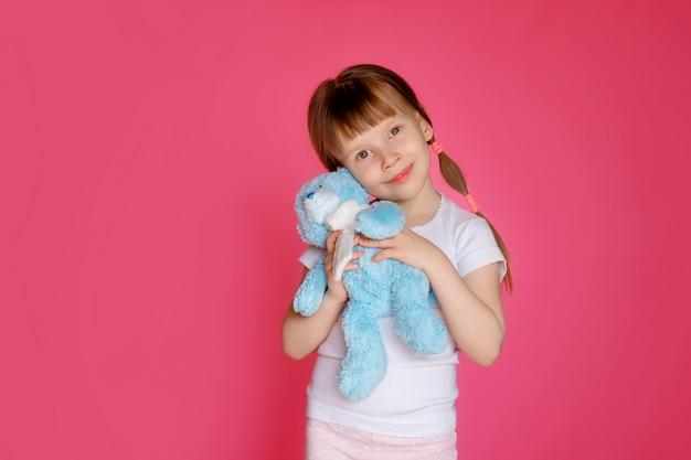 Portret van een gelukkig meisje 5-6 jaar oud op een roze muur met een teddybeer in haar handen, het kind bereidt zich voor op bed